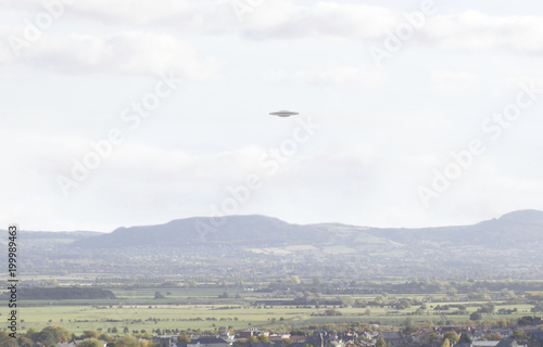 Tuinposter UFO UFO Sighting, flying saucer in the sky over a town, metallic reflective craft