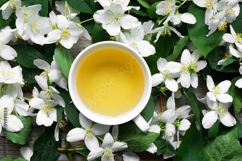 Cup of green jasmine tea on jasmine flowers background Tableau sur Toile
