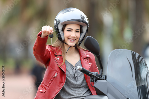 Biker showing motorbike keys on her scooter