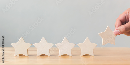 Fotografía Hand putting wooden five star shape on table