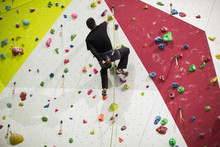 Man Practicing Rock Climbing On Artificial Climbing Wall