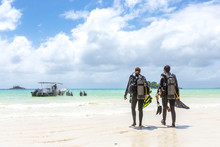 Divers Walking On Beach In Seychelles.