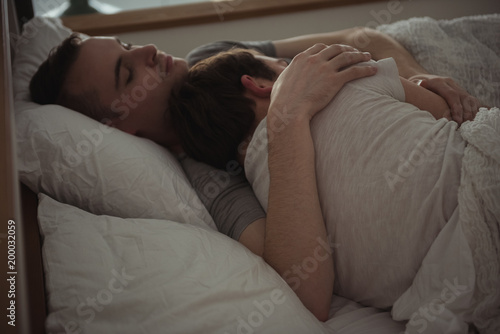 Gay couple embracing while sleeping on bed