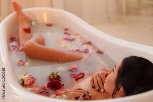 Foto op Canvas Akt Attractive girl takes a bath with milk and rose petals. Spa treatments for skin rejuvenation