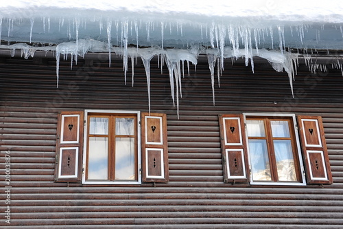 Poster Poolcirkel Large icicles hang from the roof of the house in the Alps