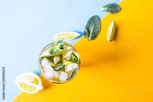 Ice tea with ice, lemon and mint on a combined colored yellow and blue background. Summer cold drink cocktail. Top view, flat lay