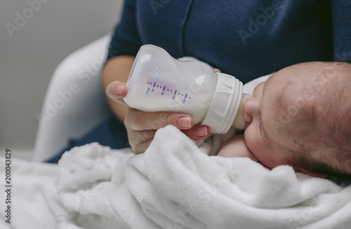 Valokuva  Unrecognizable baby detail taking feeding bottle in her mother's arms