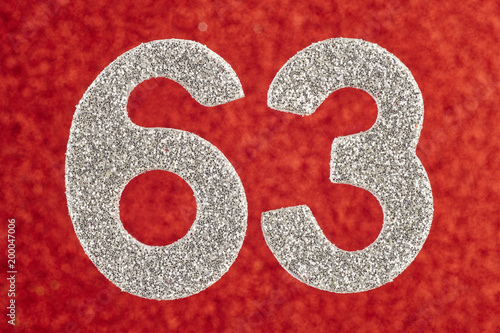 Poster  Number sixty-three silver color over a red background