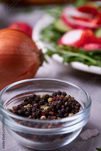 Glass bowl with dried allspice seeds with salad plate on textured background, selective focus, vertical Wall mural