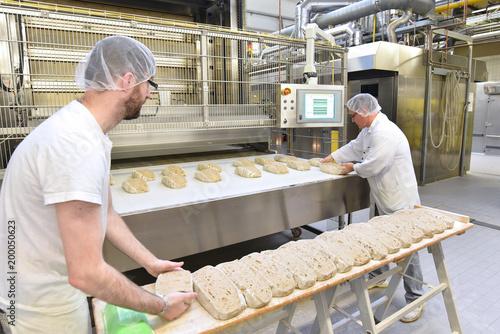Papiers peints Statue Lebensmittelindustrie: Großbäckerei - Arbeiter backen Brot // Food industry: Bakery - workers baking bread