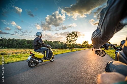 Obraz na plátně  Motor biker riding on empty road with sunset light, concept of speed and touring in nature