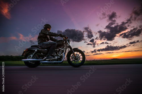 Man riding sportster motorcycle during sunset. Canvas-taulu