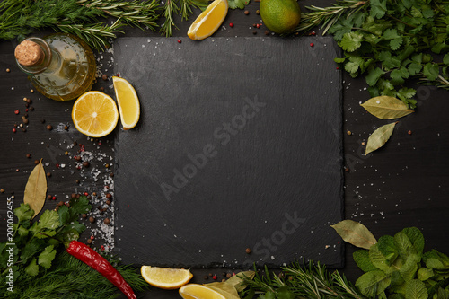 Obraz na plátne Black slate board with fresh herbs and lemon slices with olive oil