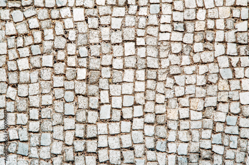 Foto op Canvas Stenen Stone pavement texture, abstract background of old cobblestone pavement close-up. Front view.