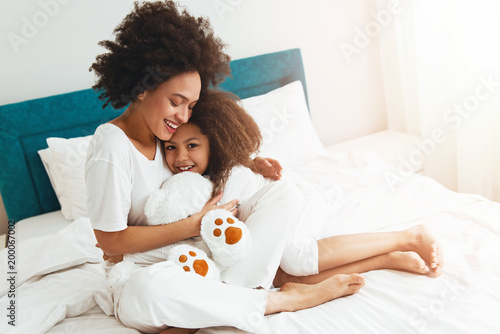 Fotografie, Obraz  Mother and daughter enjoying on the bed, happy, smiling