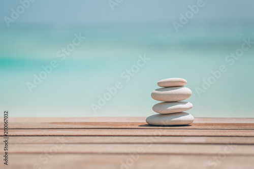 Foto op Aluminium Stenen in het Zand Zen stones on relaxing beach background. Calmness and motivational background design