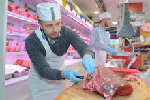 Butcher Slicing A Meat
