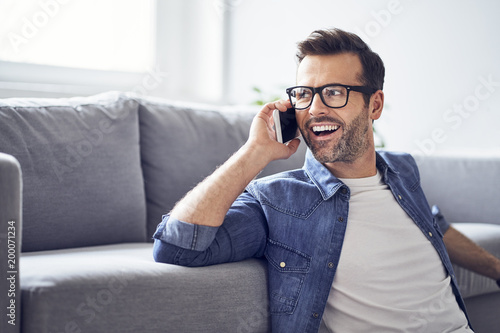 Happy man in living room talking on cell phone
