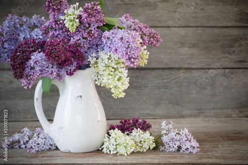 Foto op Aluminium Lilac lilac in jug on old wooden background