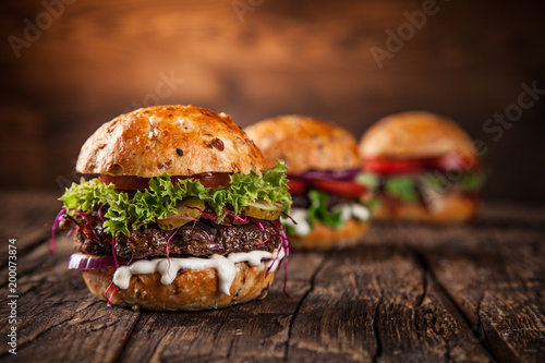 Foto op Canvas Mediterraans Europa Tasty burgers on wooden table.