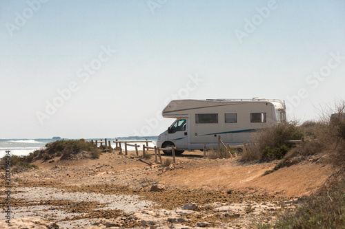 Fotografía Caravan motorhome parked on the beach in front of the blue sea in a beautiful pl
