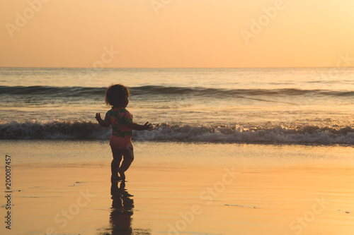 01fc95e71 Image of Cute baby girl is running at the beach near the sea shore and  enjoying