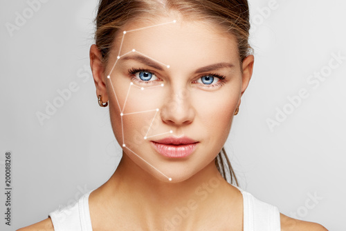 Skin care and technology. Portrait of beautiful woman face with drawn massage lines.