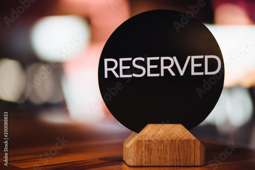 Fotografiet Close up of restaurant reserved table sign on table
