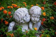 ANGELS IN LOVE. Sculptures Of Boy And Girl Angels Surrounded With Flowers Hugging And Cuddling. The Boy Angel Is Kissing Her By The Cheek.