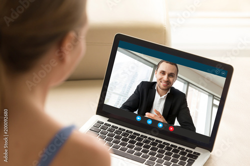 Fototapeta Young woman communicating with man in formal suit via video call application. Young couple chatting. Long distance relationship, virtual communication. Close up view over shoulder, focus on screen. obraz na płótnie