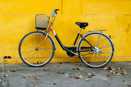 Fotobehang Fiets Old bicycle on a background of bright painted yellow wall and autumn leaves on a street.