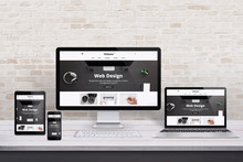 Multiple Display Devices With Modern Flat Design Web Site Presentation. Wooden Desk And Brick Wall Interior.