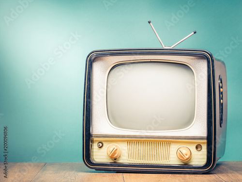 Retro old TV set receiver on table front gradient mint green wall background. Broadcasting concept. Vintage style filtered photo