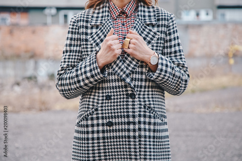 Photo  detail shot of a woman outdoors posing in a checked patterned coat, wearing a golden ring and watch and holding a black backpack