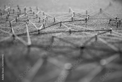 Background. Abstract concept (idea) of network, social media, internet, teamwork, communication abstract. Nails linked together by threads. Isolated. Entities connected.