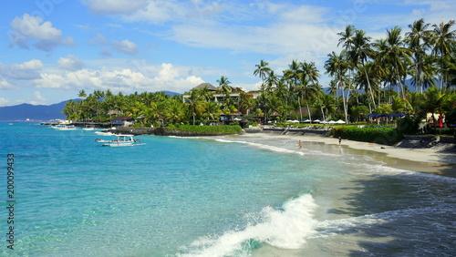 Fotografija  malerischer Urlaubsstrand in Candidasa in Bali mit Meer, Wellen und grünen Palme