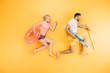 Leinwandbild Motiv happy young couple holding beach umbrella and swimming ring on yellow, summer vacation concept