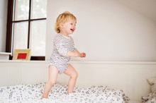 Cute Toddler Boy Jumping On Th...