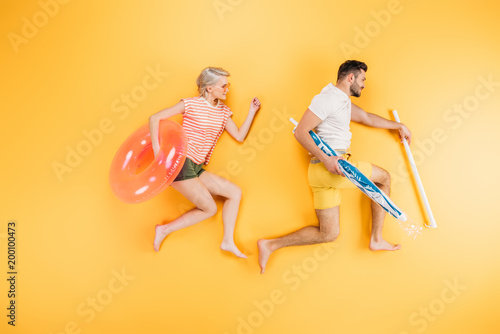 happy young couple holding beach umbrella and swimming ring on yellow, summer vacation concept