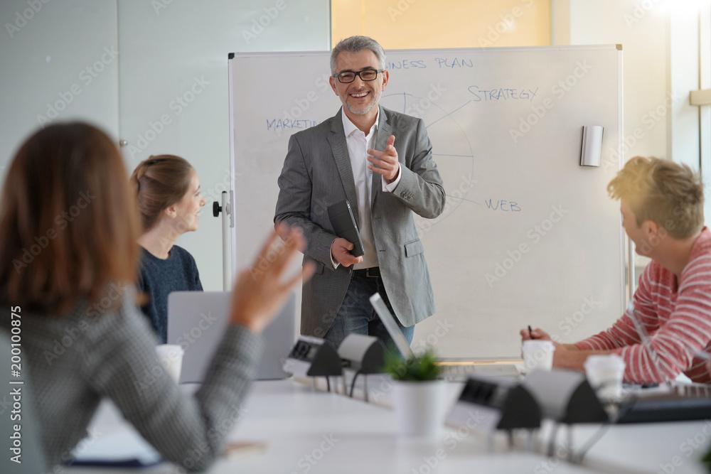 Fototapeta Teacher giving economics class, using whiteboard