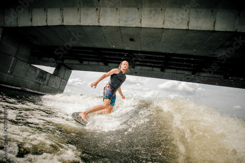 Poster Nautique motorise Athletic long-haired man wakesurfing on the board under the concrete bridge