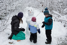 Mother With Children Making Snowman