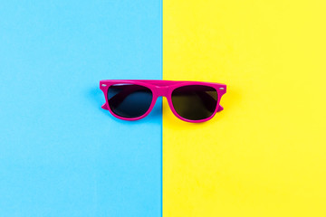 Red sunglasses on bright blue and yellow background.