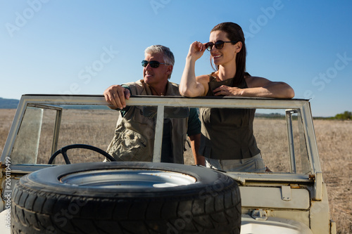 Couple looking away while standing in vehicle on field
