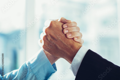Fotografiet  Close-up of two clasped hands of businessmen as sign of strong partnership or team