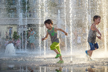 Happy Kids Have Fun Playing In City Water Fountain On Hot Summer Day.