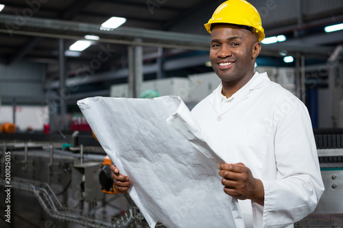 Smiling male worker reading instructions at juice factory
