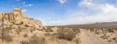Dirt road wraps around pile of large rock boulders in the southern desert of California.