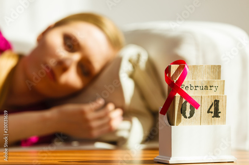 Woman on bed, world breast cancer day on calendar - Buy this