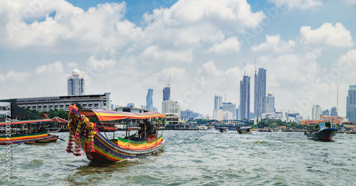 Tourist popular boat travel on the Chao Phraya river. To stay in downtown Bangkok. King Rama I Memorial Bridge and skyscrapers of Chinatown is seen on the horizon